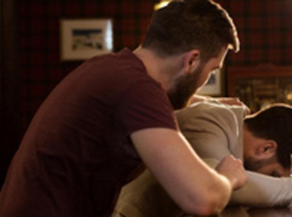 Один парень лежит лицом на столе, друг пытается его успокоить