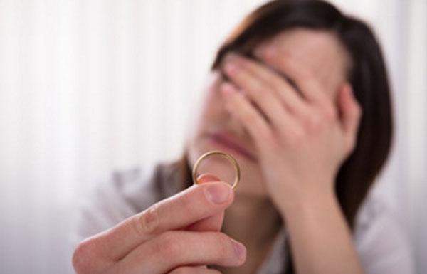 Женщина держит обручальное кольцо. Лицо закрыла руками