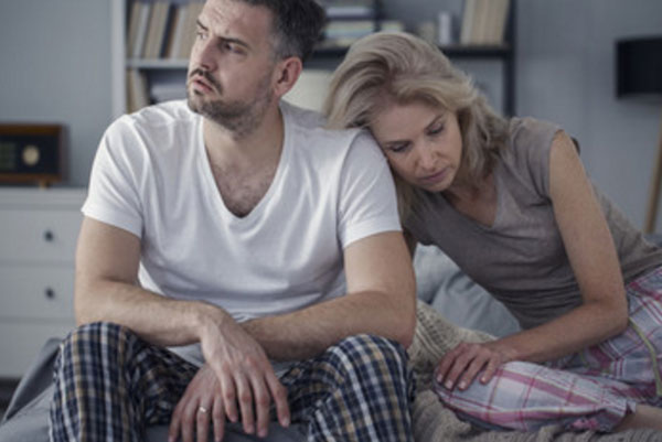 Муж с женой сидят на кровати. Мужчина отвернулся