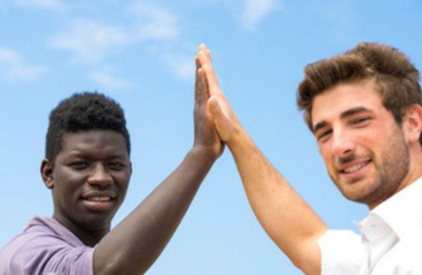 Мужчина европеоидной расы прижимает ладонь к ладони мужчины негроидной расы