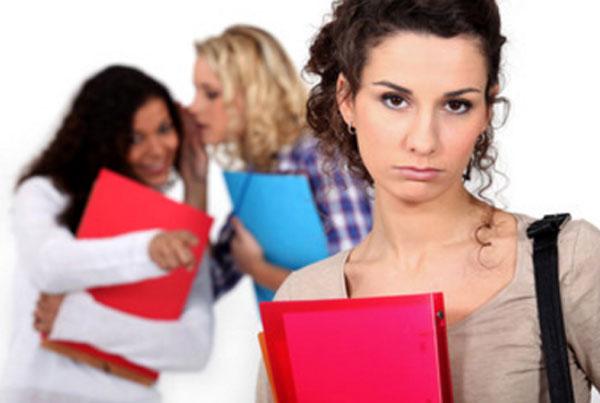 На переднем плане расстроенная девушка. Сзади нее две девушки, которые осуждают и насмехаются над ней