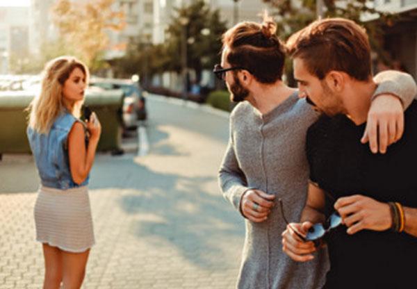 Два мужчины смотрят вслед уходящей женщине