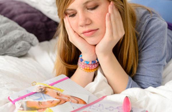 Девушка лежит на кровати и рассматривает фотографии любимого мужчины, наклеенные в тетрадке