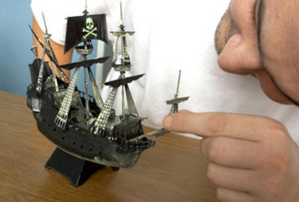 Мужчина собирает модель корабля