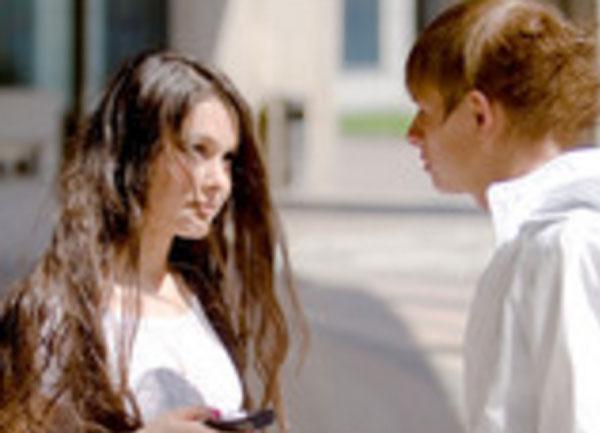 Парень стоит близко с девушкой. Она смотрит на него
