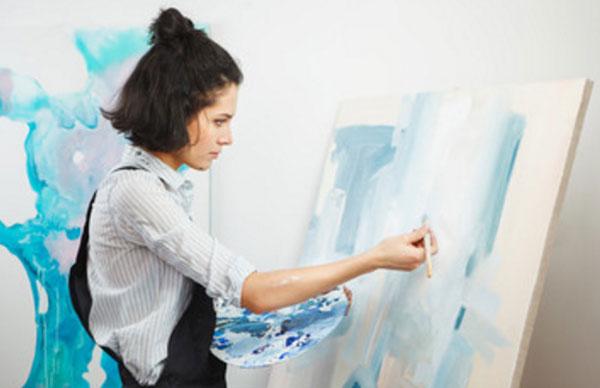 Девушка рисует на мольберте