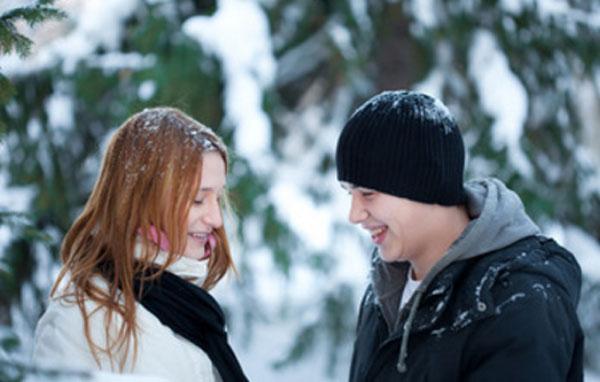 Девушка с парнем стоят друг напротив друга в зимнем парке
