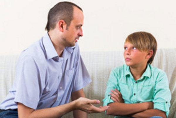 Отец что-то объясняет расстроенному мальчику
