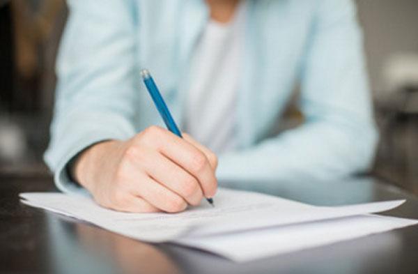 Мужчина что-то пишет на листке бумаги