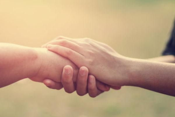 Один человек держит за руку другого