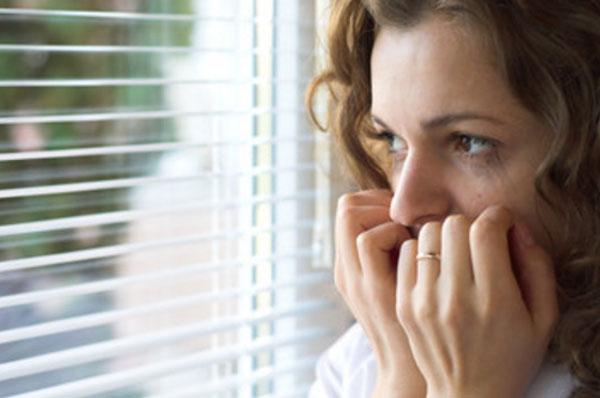 Женщина смотрит в окно. На ее лице виден страх