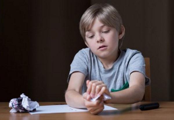 Задумчивый мальчик сидит за столом и комкает листки бумаги