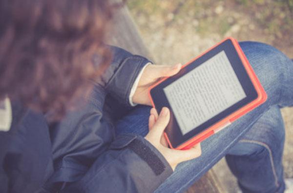 Женщина читает электронную книгу, сидя в парке на скамейке
