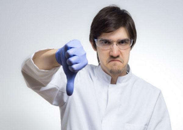 Сердитый мужчина в очках и перчатках показывает большой палец вниз
