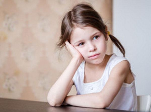 Печальная девочка сидит за столом