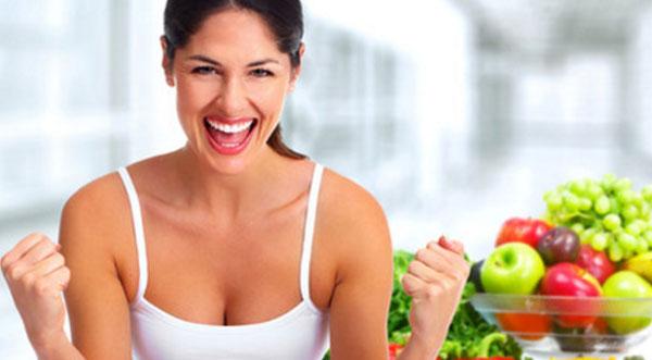 Женщина радуется. Рядом с ней миска с фруктами