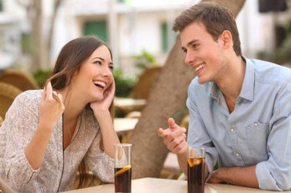 Парень с девушкой сидят в кафе за столиком. Улыбаются