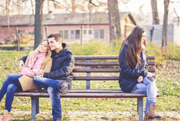 С одной стороны скамейки сидит парочка. На другом конце грустная девушка