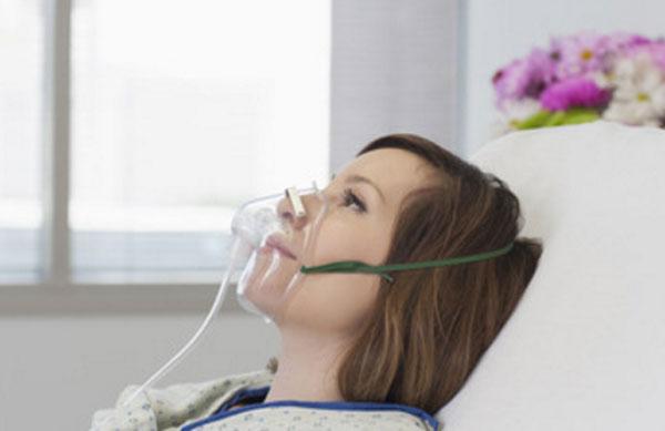 Женщина лежит в больнице с кислородной маской на лице