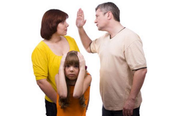 Мужчина замахивается на свою жену. Девочка в ужасе, прикрывает уши руками