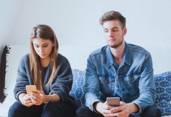 Парень с девушкой сидят на диване, у обоих в руках телефоны. Девушка смотрит в свой экран, а парень аккуратно подглядывает