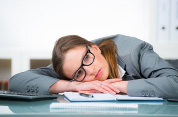 Девушка в костюме и очках лежит на рабочем столе. У нее грустный взгляд