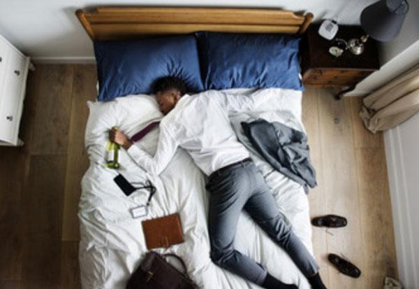 Уставший мужчина лежит на кровати в уличной одежде