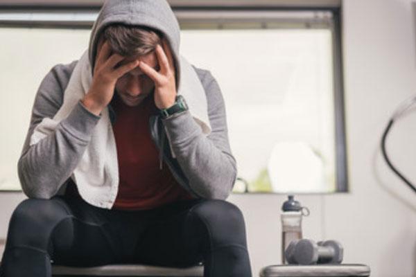 Уставший мужчина сидит после тренировки