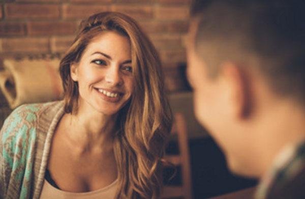 Девушка общается с мужчиной. Она улыбается