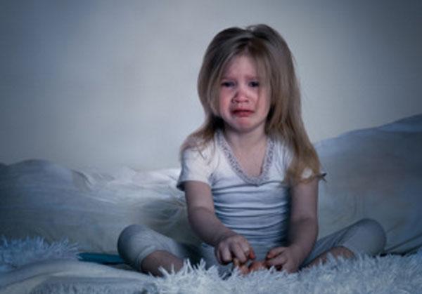 Заплаканная девочка сидит в темной комнате