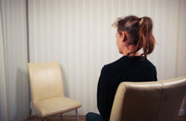 Девушка сидит напротив пустого стула. Смотрит на него