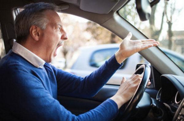 Мужчина сидит за рулем машины и на кого-то матерится