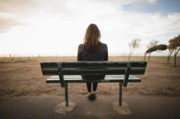 Девушка сидит на одинокой скамейке