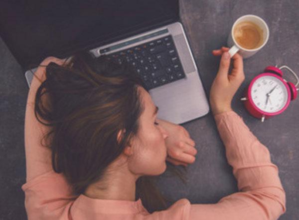 Девушка спит на ноутбуке, рядом чашка с кофе и будильник