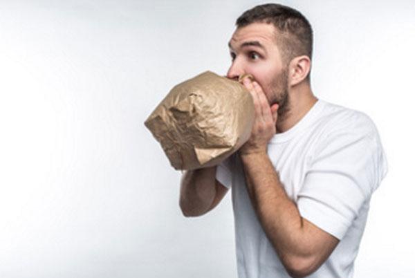 Мужчина дышит пакет. У него паническая атака