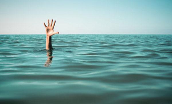 Рука человека, который тонет, возвышается над водой
