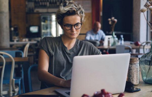 Женщина в очках, простой серой футболку, растрепаной прической и без макияжа печатает на ноутбуке