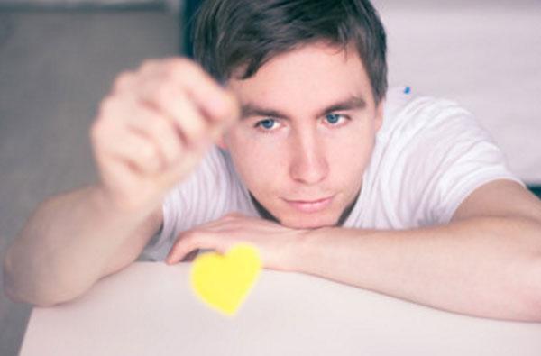 Задумчивый парень играет картонным сердечком