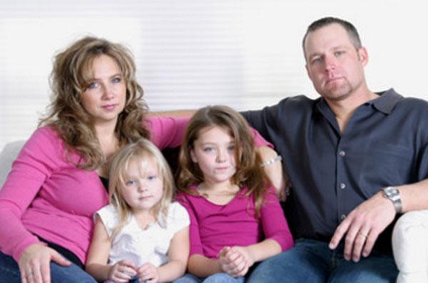 Серьезные муж с женой. Рядом с ними сидят две дочки