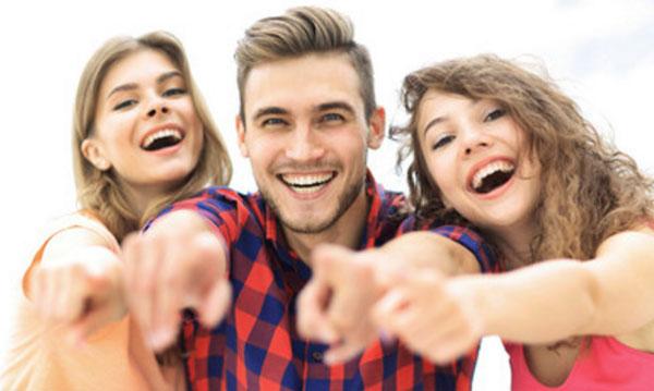 Парень и две девушки улыбаются и указывают пальцем в камеру