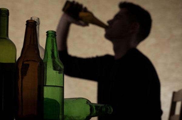 На столе пустые бутылки. На стене видна тень мужчины, который пьет спиртное с горла бутылки
