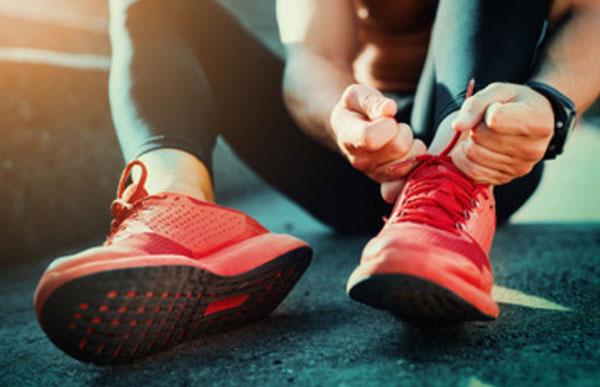 Мужчина завязывает шнурки на спортивной обуви