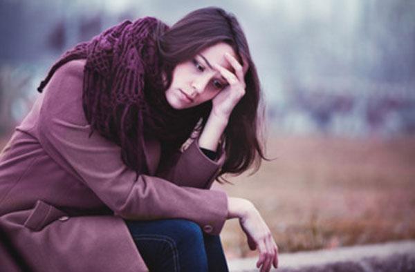 Одинокая девушка сидит на улице