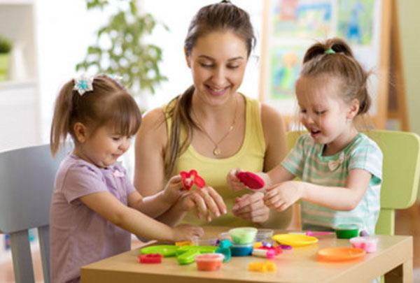 Женщина сидит за одним столиком с двумя девочками, играет с ними