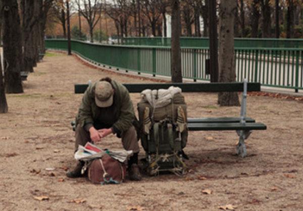 Мужчина сидит на скамейке. Перед ним сумка, рядом походный рюкзак