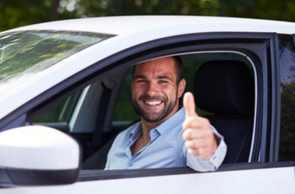 Счастливый мужчина за рулем машины