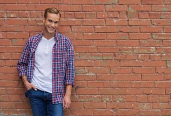 Одинокий улыбающийся мужчина стоит возле кирпичной стены