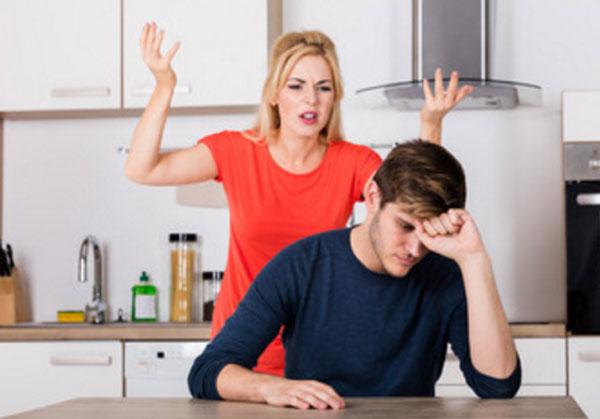 Расстроенный мужчина сидит за столом. Сзади его жена высказывает накипевшее