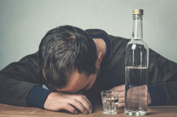 Мужчина уснул на столе. Перед ним бутылка водки с рюмкой