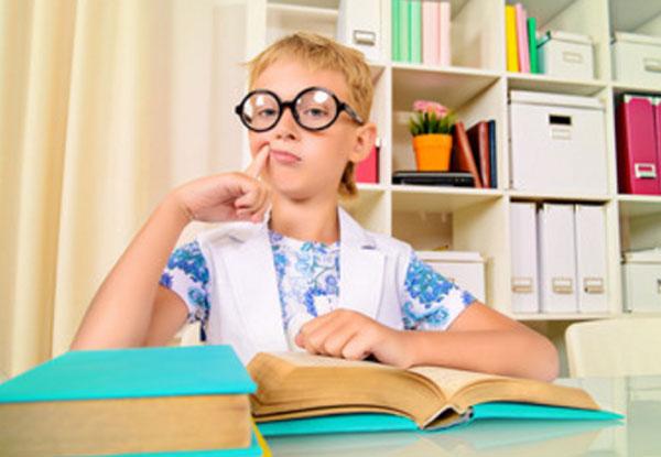 Мальчик в очках сидит за толстыми книгами